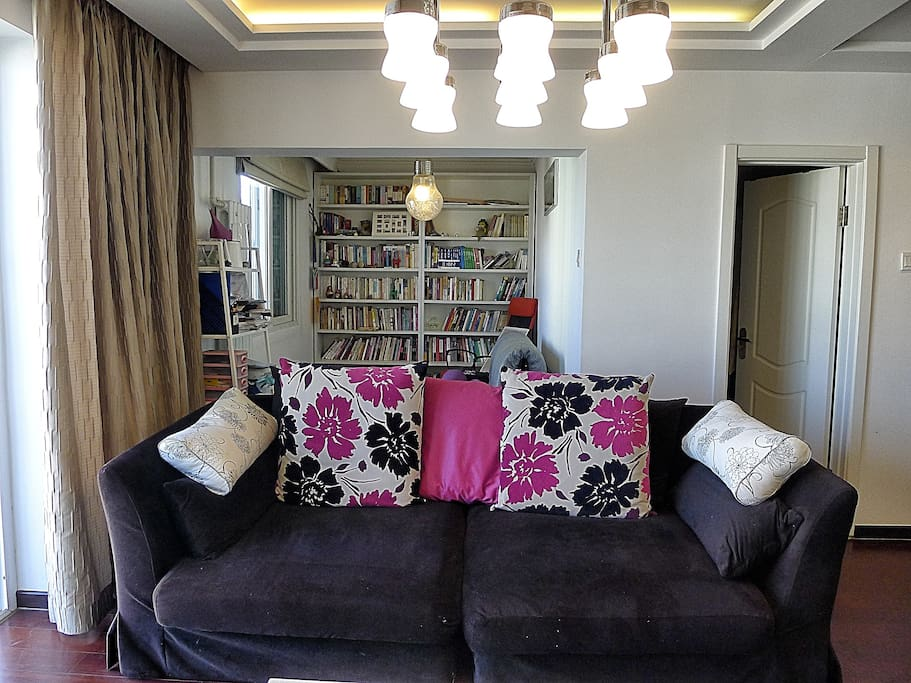 behind the sofa, there is a small room for books