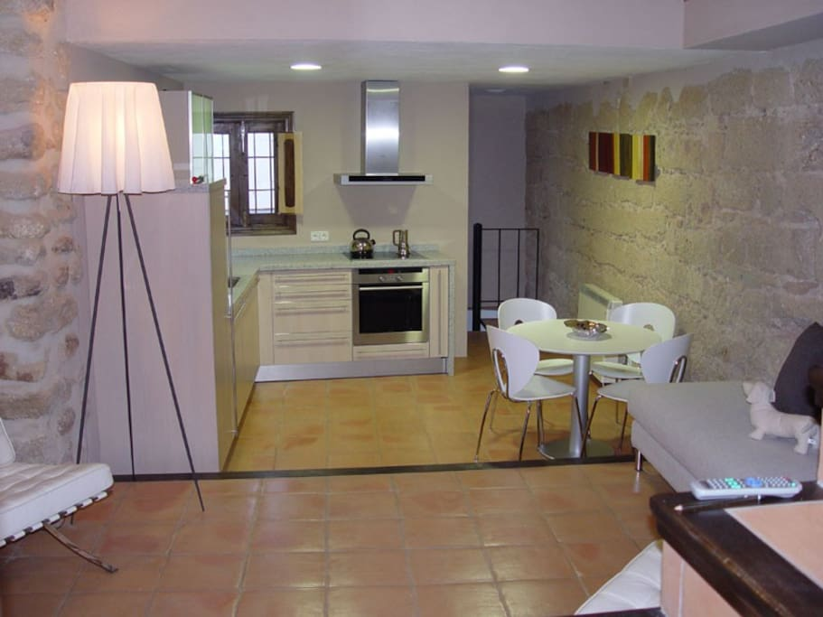 Open plan living, modern kitchen with oven and dishwasher.