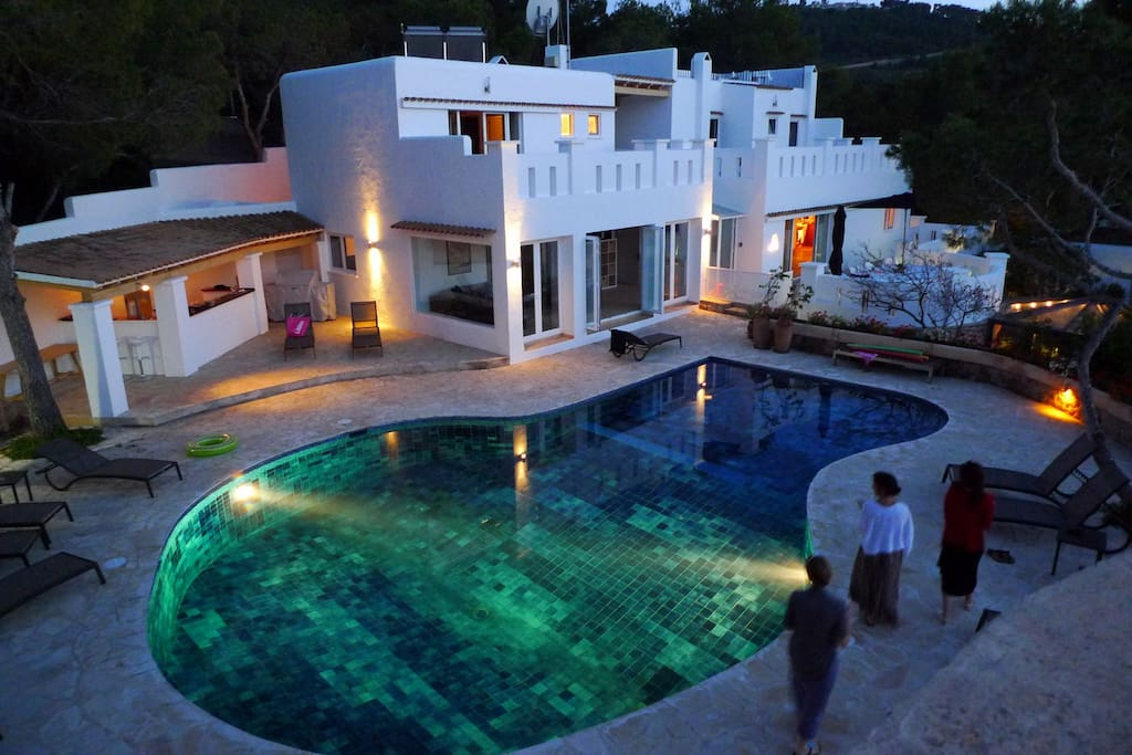 The villa, outdoor bar and pool lit up by night