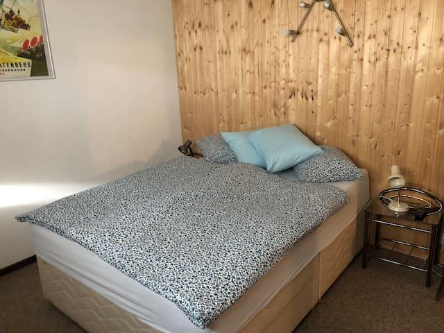Schlafzimmer 1 UG mit Boxspringbett und TV. Fenster und Notausgang.