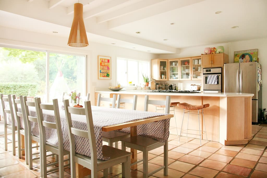 large eat in kitchen with farm table that seats 12 and 3 counter top bar seats