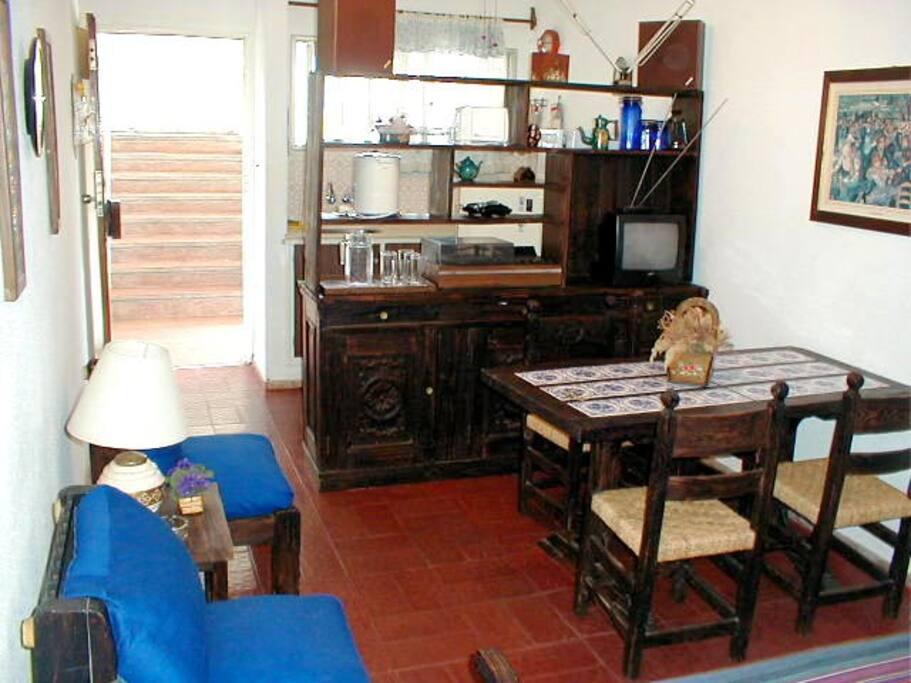 Living comedor. Mueble con equipo de audio y TV. Detrás está la cocina.