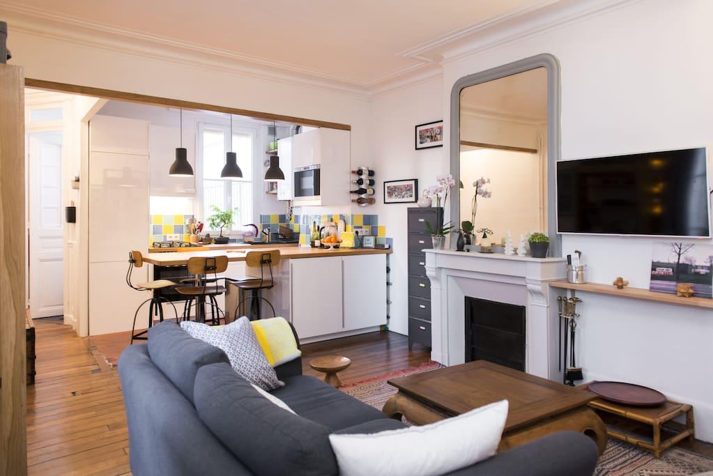 Le pièce principale avec le canapé confortable et la cuisine ouverte