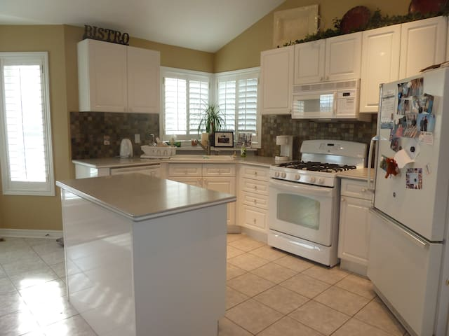 Bright kitchen w. island, casual table for 8, walk out to deck