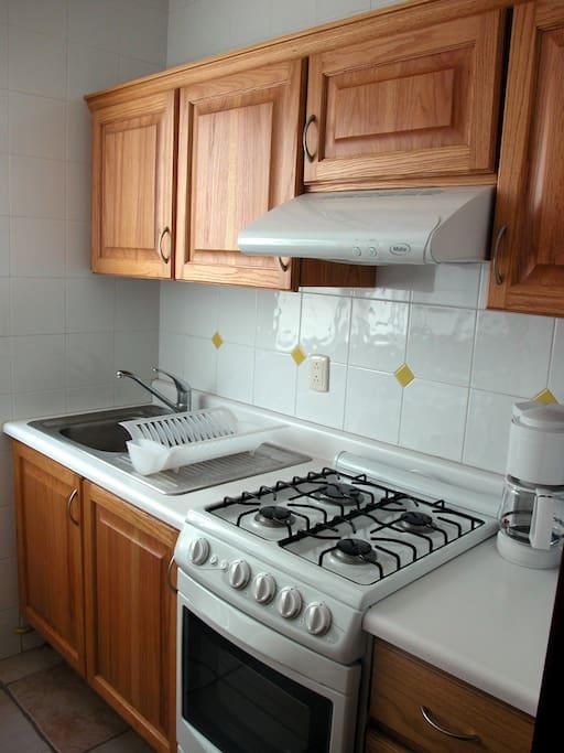 cocina con horno, 4 quemadores, equipada con microondas, cafetera, tostados, y servicio para 4 personas.