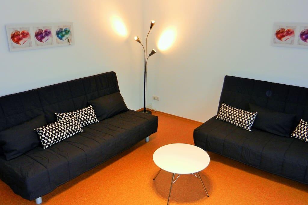 Wohnzimmer mit zwei Couchen die in zwei Doppelbetten verwandelt werden können