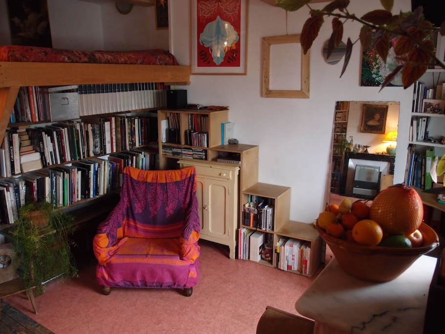 Le lit 2 places en mezzanine optimisée, surplombant son étagère-escalier atypique.