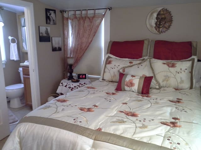 A queen size bed with fine linens and an adjoining bathroom.