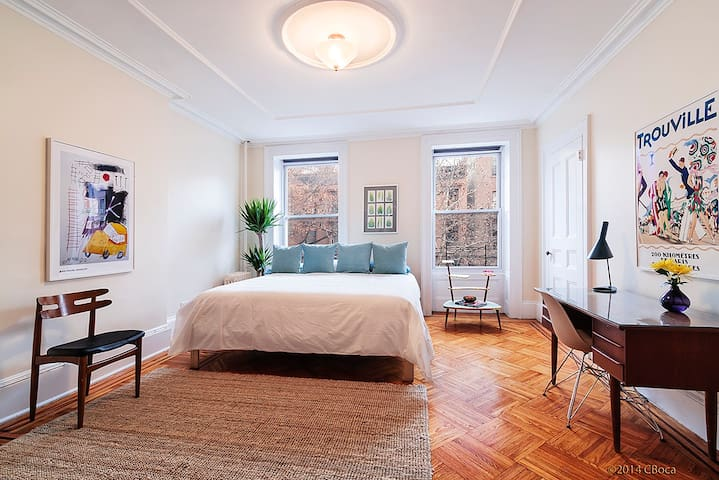 King sized bed in large spacious master bedroom with period details.