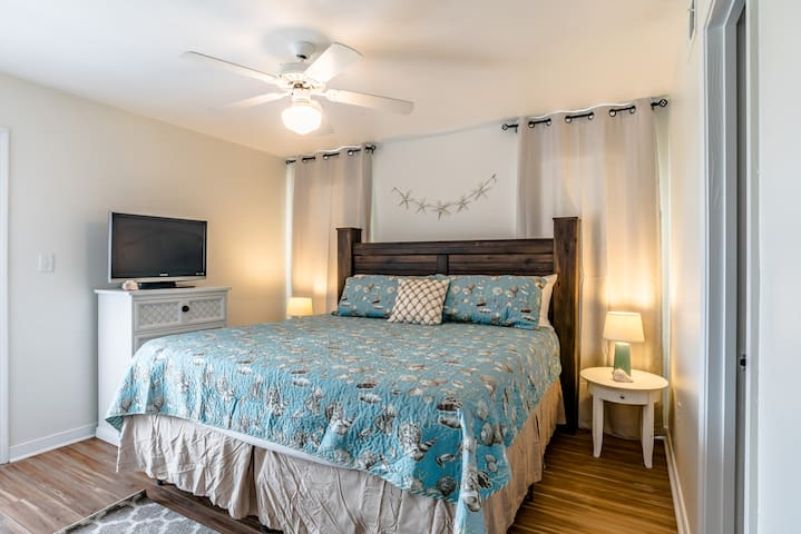 1st floor king bedroom with 32 inch TV and oceanside balcony. has in room access to full bath.