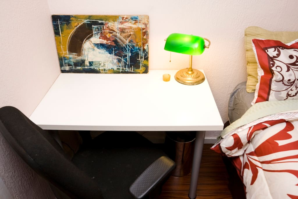 A comfortable chair, a banker's lamp, a desk, and a modern painting