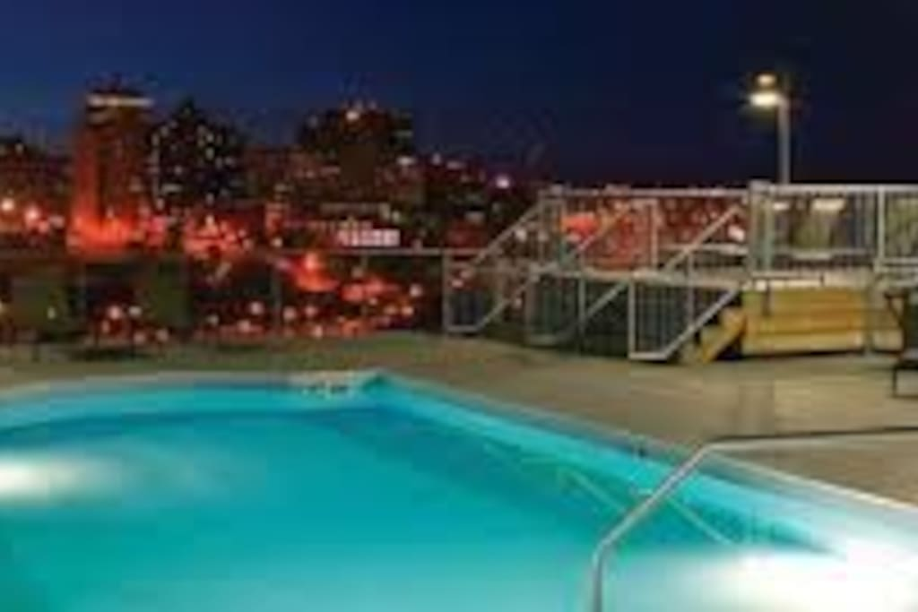 Rooftop pool at night overlooking the city.