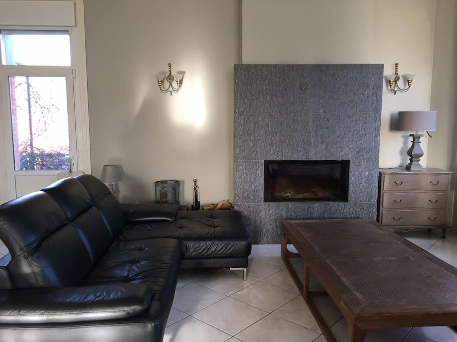 Pièce de vie principale spacieuse et lumineuse comprenant 2 canapés d'angle et une cheminée.