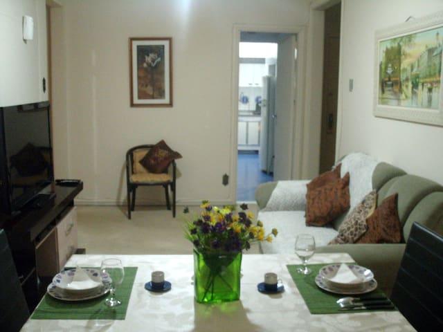 Sala com sofá, mesa de jantar, televisão 46 polegadas, TV a cabo, internet WI-FI, DVD e estação de trabalho.