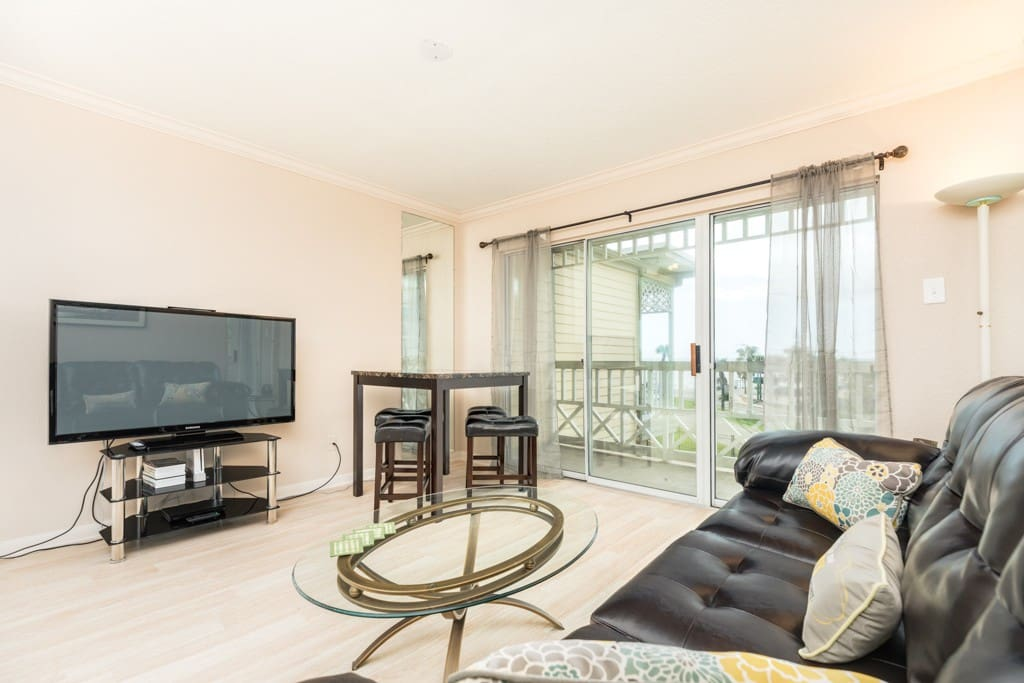 Leather sofa, flat screen TV, dining table, and balcony access in the living area