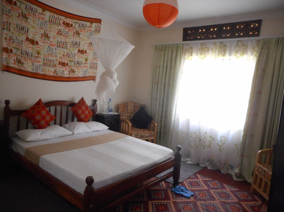 Room with a Double bed and Mosquito net.