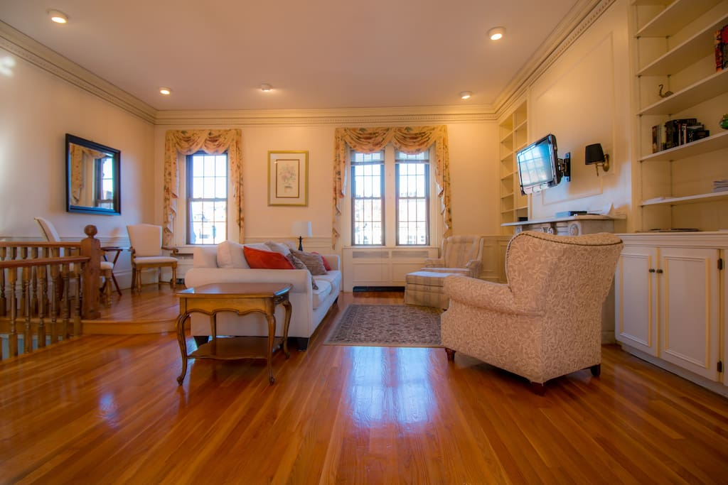 Space and light in the exquisite Victorian era  living room with central AC oozes luxury and charm.  It's big enough for 100 people, with large bay windows looking  Charles Street and Beacon Hill.  HDTV wireless internet and books for browsing.