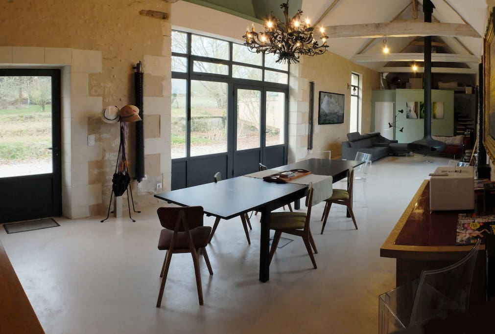 view of the main living room, seen from the entrance to the kitchen. There is a small breakfast table, a few comfortable sofas around a modern designer fireplace. In the background you can see the mezzanine with a library, an artists workspace and a clic clack sofa bed