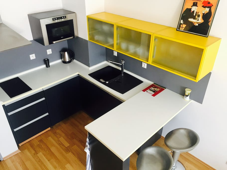 Fully equipped modern kitchen with microwave and cooktop.