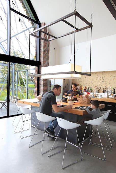 La partie cuisine de la pièce à vivre. Pour 7 couverts confortablement. Table de cuisson intégré à l'îlot central. Réfrigérateur, cave à vin, congélateur.