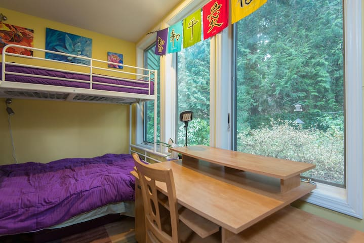 Sunriver bedroom with a twin over full bunkbed.  Door to outside deck.  Desk and dresser.