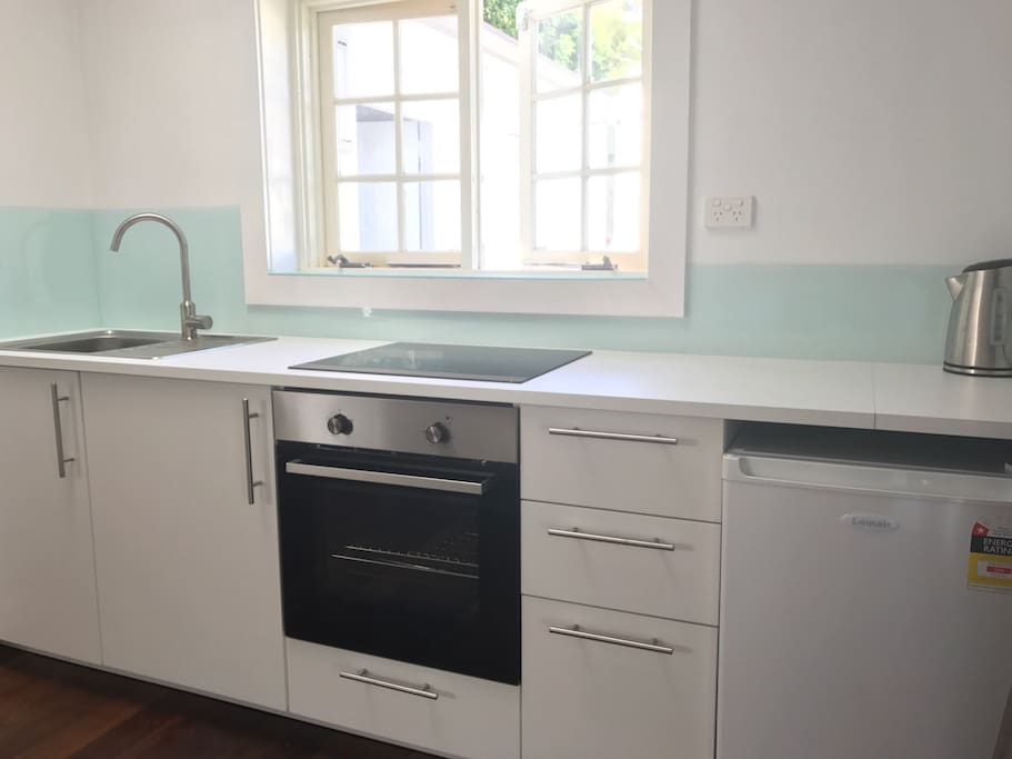 Brand new kitchenette with oven, cooktop, bar fridge and kettle.