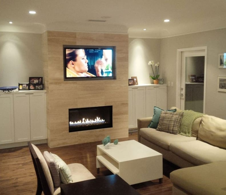 Living room with L-shaped couch, connected to the kitchen with TV and built-in home speaker system.