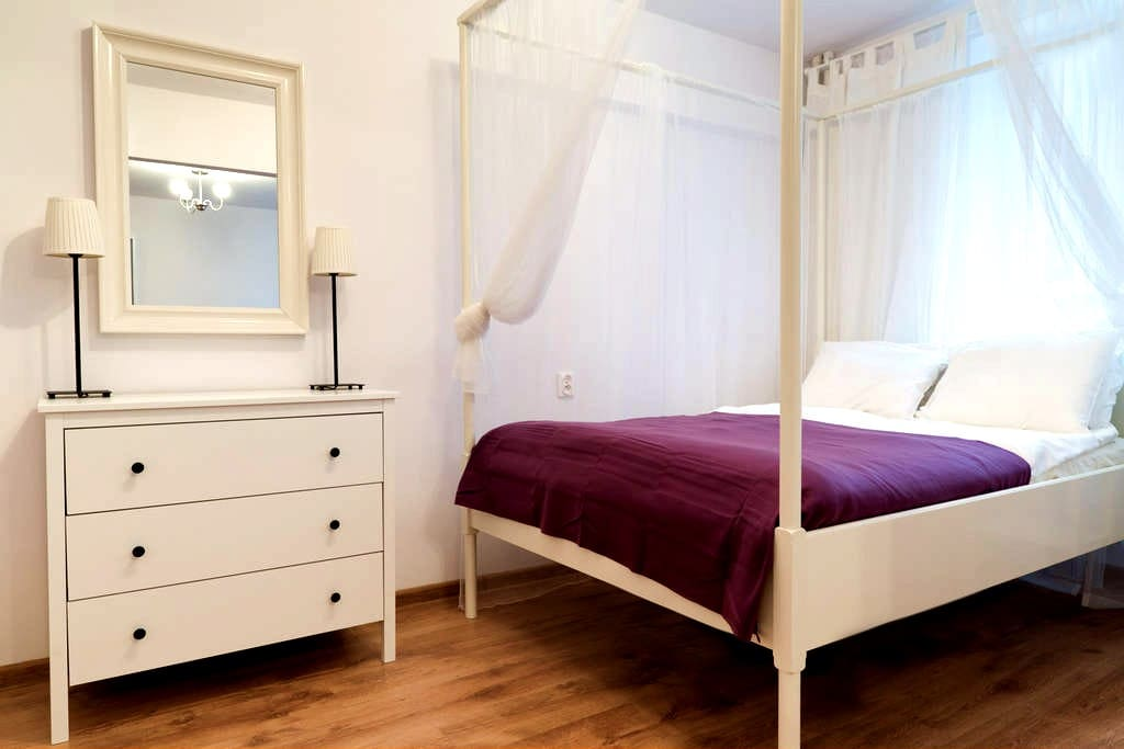 Bedroom with large canopy bed and dresser