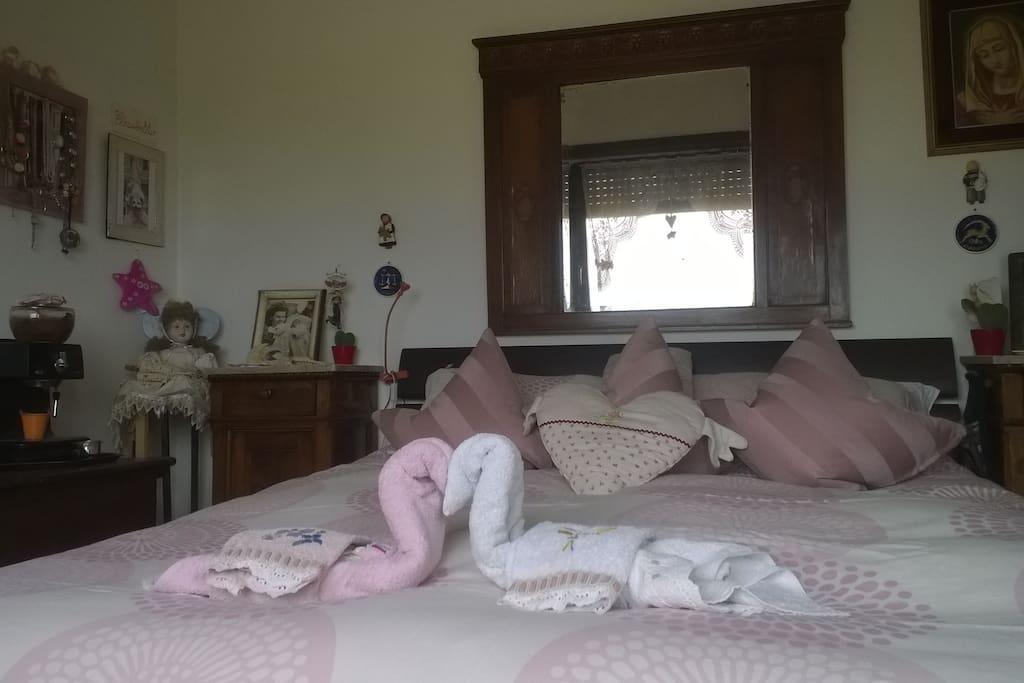La stessa camera con il copriletto rosa pronta per gli ospiti ...