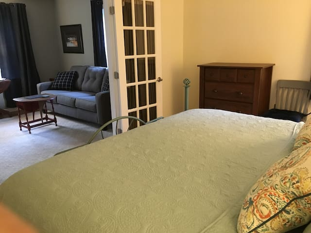 View from bedroom into living room King size bed with window facing north and the orchard, as well as the French doors into the living room.