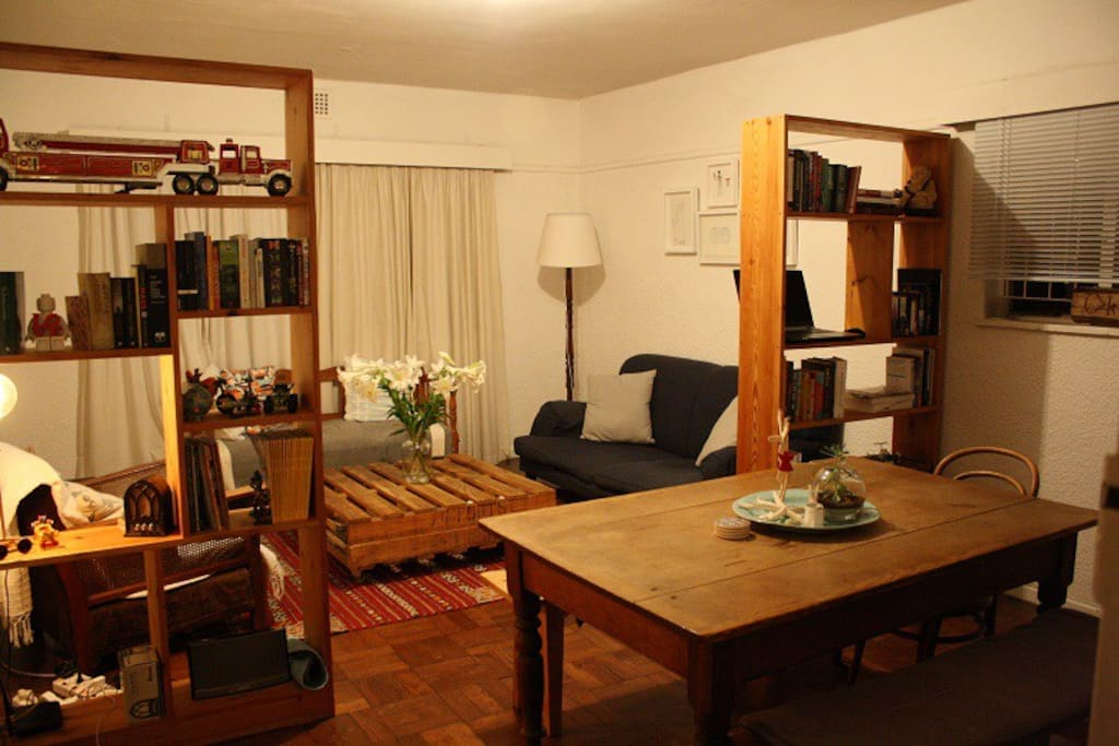 Living room with 2 couches, dining table + benches, bookshelves (with books)