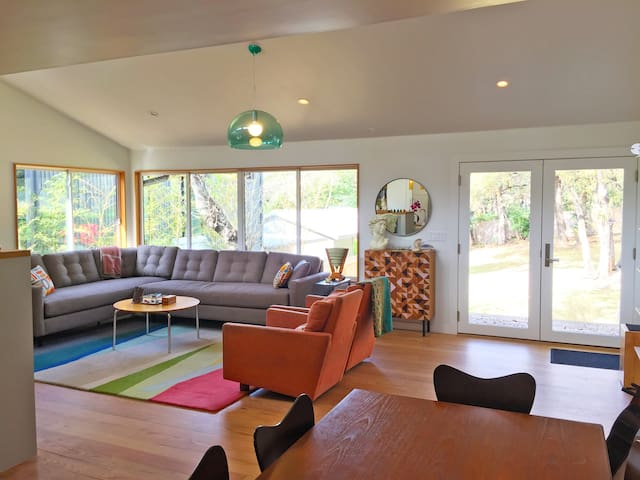 Large, open living room that looks out onto tree covered back yard.