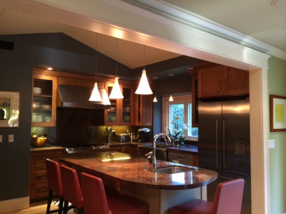 Chef's kitchen with island and seating for entertainment and breakfast. Dramatic wood coffered ceiling