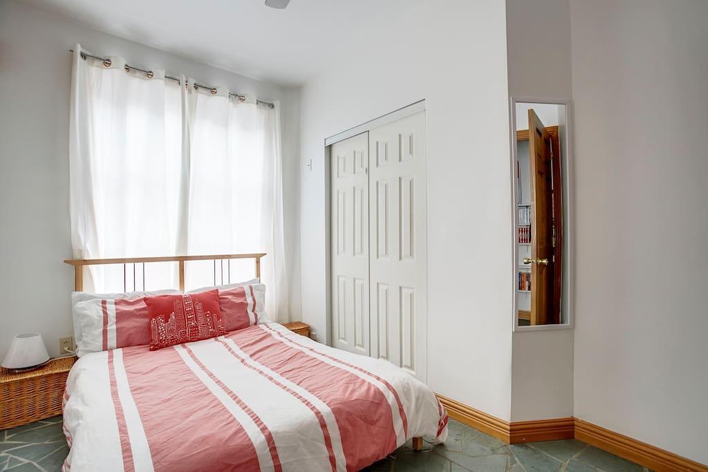 Chambre lumineuse avec lit double et grand placard.