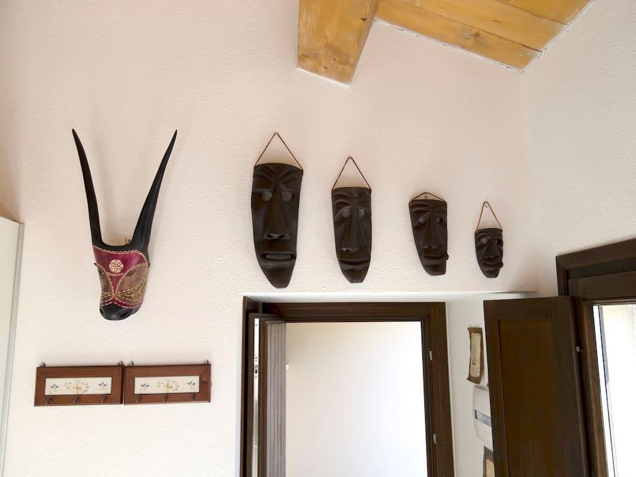 Maschere di artigianato sardo sopra la porta d'ingresso