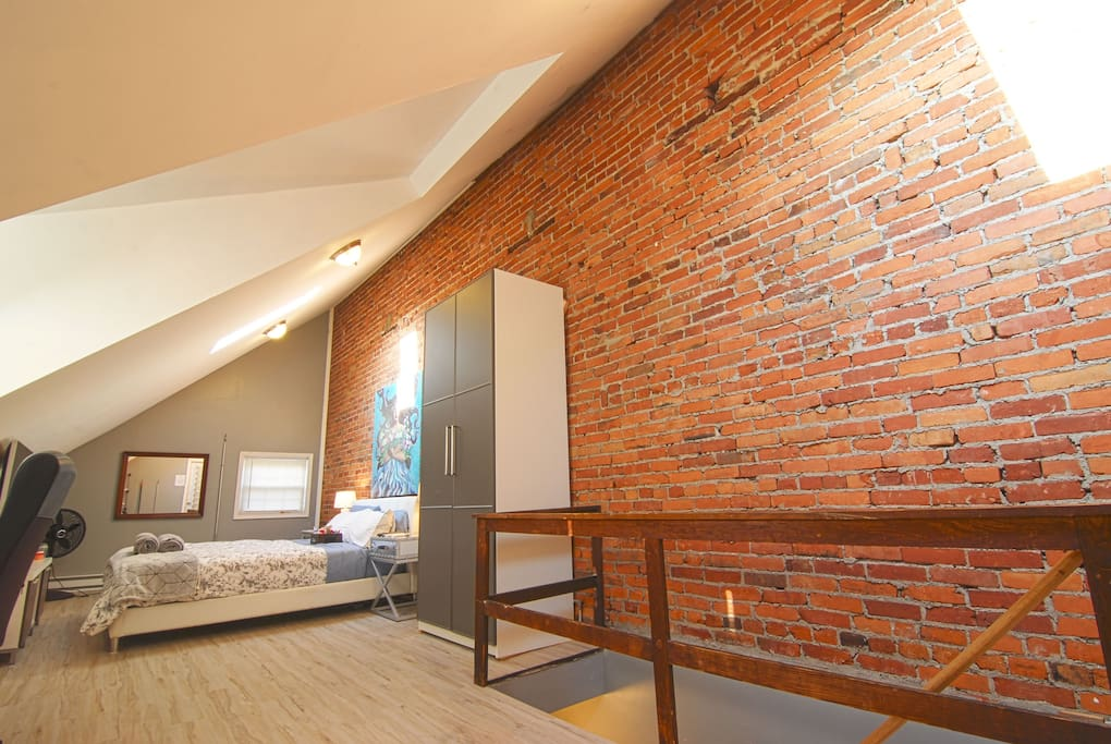 The loft measures 10x30 ft with a 13 ft tall raw brick wall.