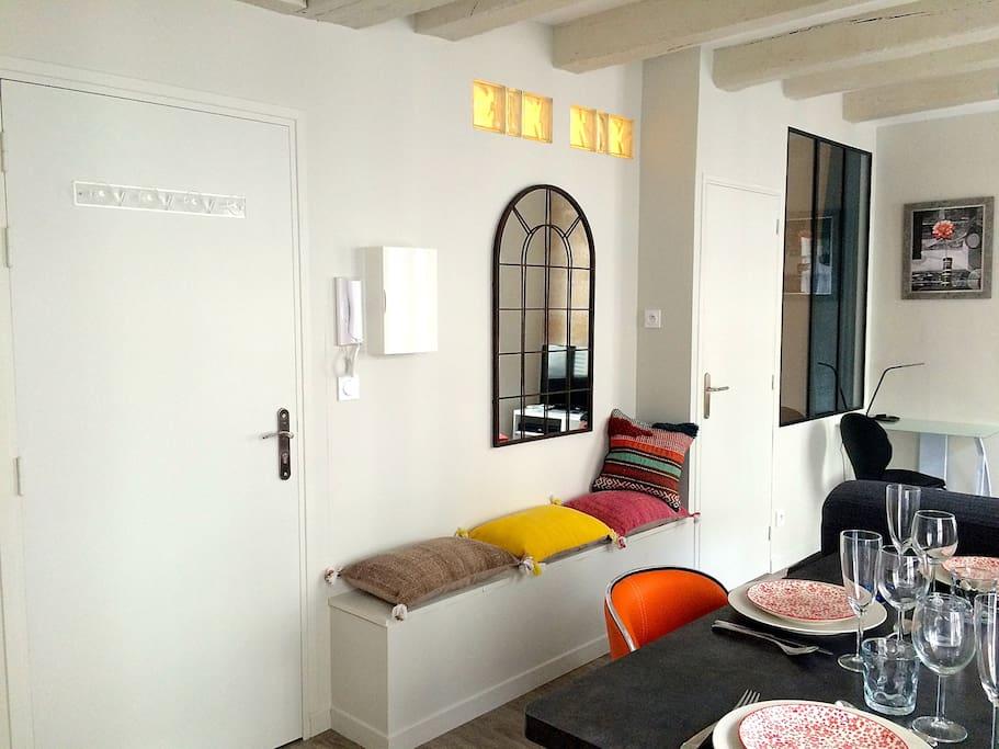 Entrée de l'appartement (sous les coussins se trouve un coffre de rangement).
