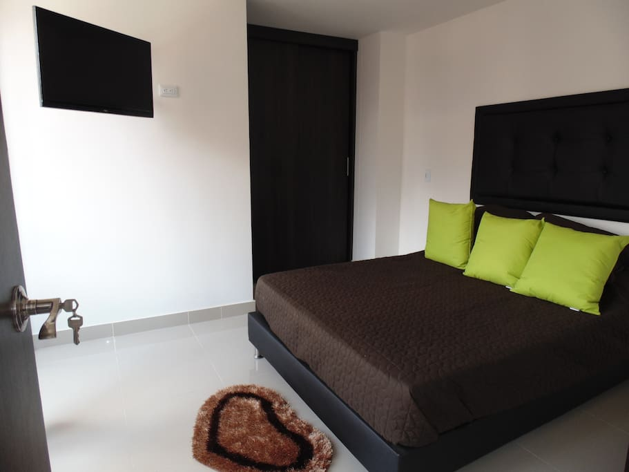 Queen size bed main room with private bathroom and tv