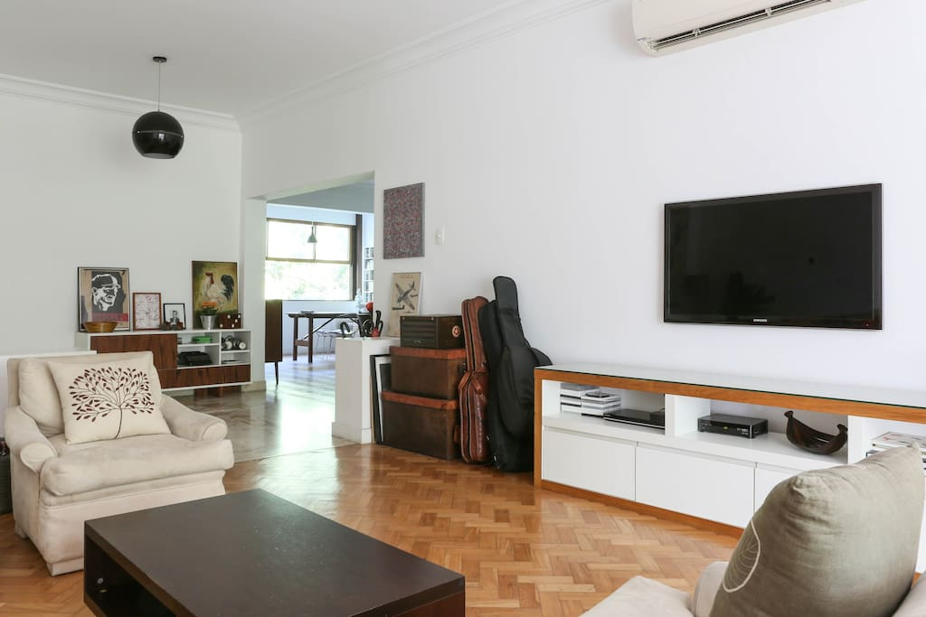 Entrance hall, living room with flat-screen TV, and separate dining room in the background.