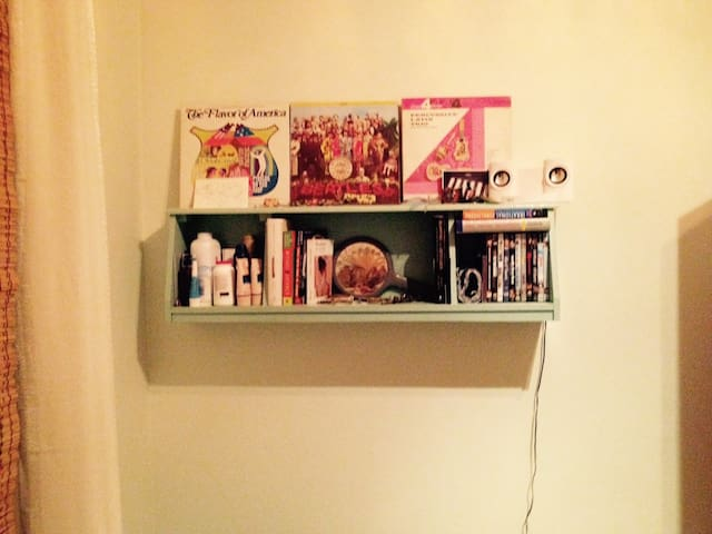 Shelf in your room with books and movies at your disposal