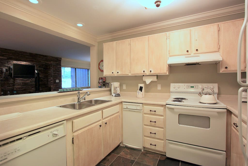 Spacious kitchen with slate flooring and new appliances.
