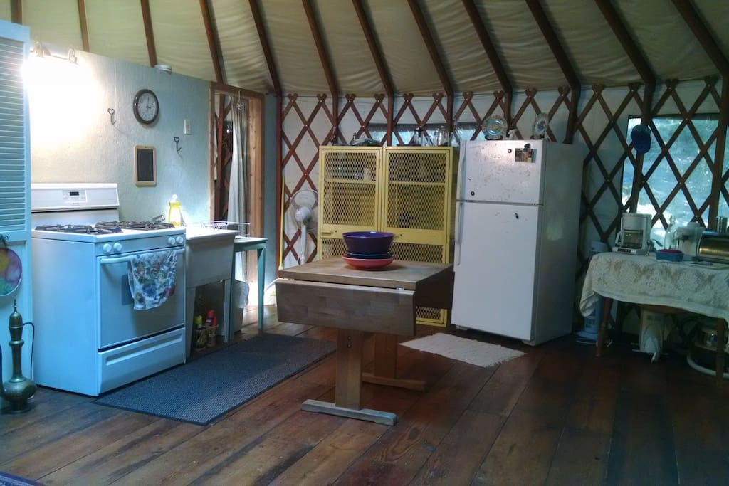 Kitchen w/propane stove/range, deep utility sink, apartment size fridge, vintage lockers (from U of O Hayward Field's west grandstands) with dishes, glasses, mugs, cooking and serving utensils, microwave, coffee/latte maker, butcher block table.