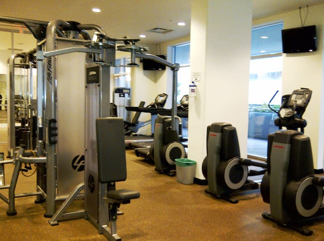 24.  Modern gym equipmentsand overhead flat screen TVs.