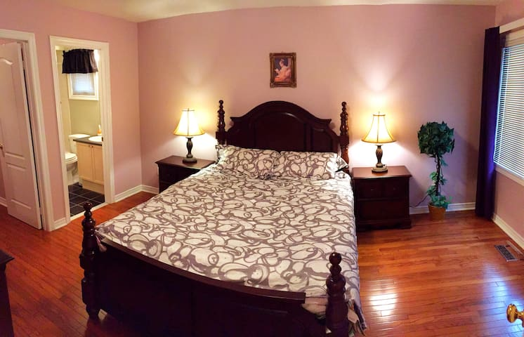 Beautiful second master bedroom ensuite with queen size bed, desk, bathroom and walk-in closet.