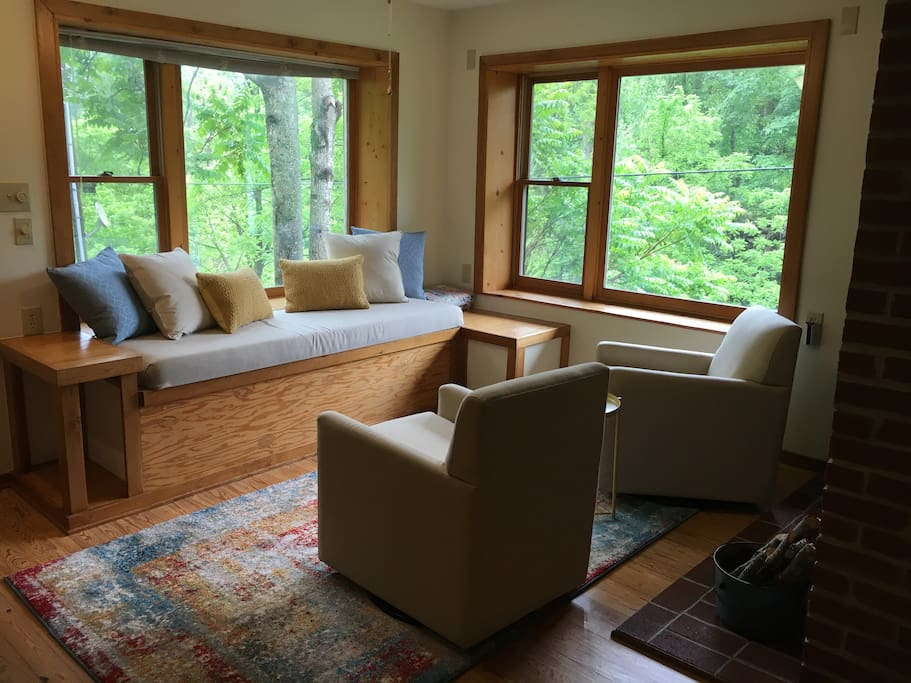 Front living room has window seat with picture windows.  Perfect place for a nap  or just to watch the water flow below
