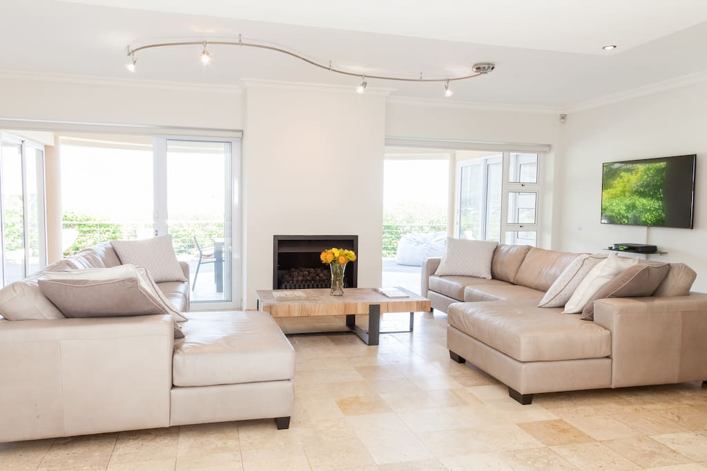 Shared lounge with comfortable leather sofa's, a gas fire place and doors leading out on to the private patio with pool and built in gas bbq
