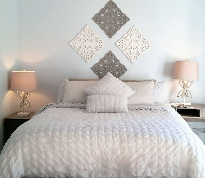 Comfy Queen size bed is the centerpiece of this professionally designed and intentional space