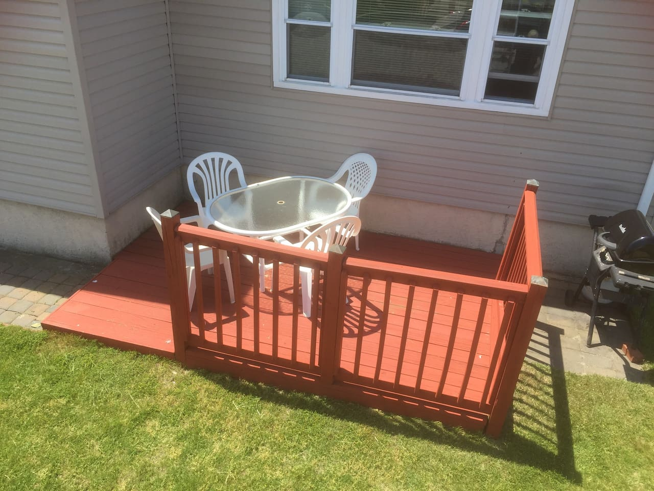 Deck with patio furniture and gas BBQ in front of property.