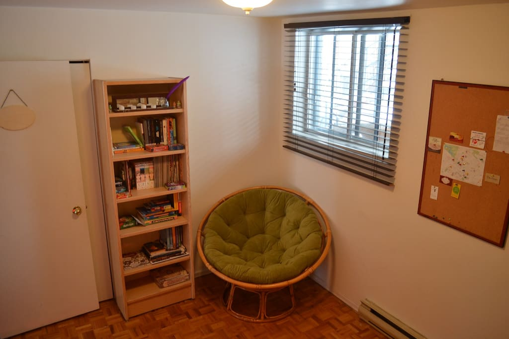 Papasan chair and a bookshelf added. Books in English, French and Portuguese, as well as board games