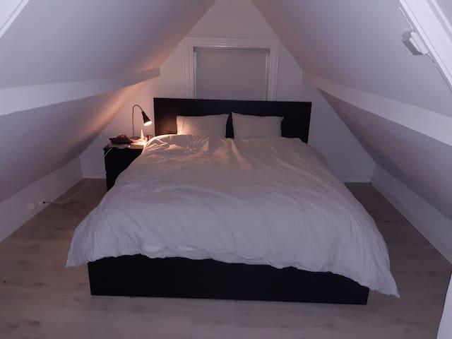 Dobbeltseng i loftstue, hvor det også er sofa og stort TV.